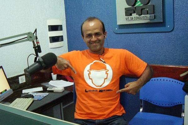 Homem sentado e sorrindo em um estúdio de rádio aponta para uma ilustração em sua camisa de cor laranja. À sua volta, estão duas bancadas, microfone, teclado, computador e papeis sobre a bancada da esquerda e, ao lado direito, uma cadeira azul de plástico vazia.