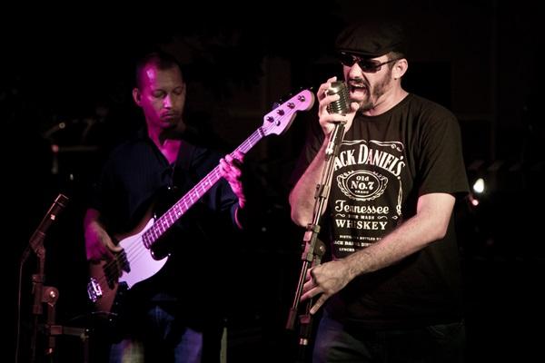 Dois homens se apresentando num palco. À esquerda, homem negro com blusa de manga comprida na cor preta e calça jeans toca baixo. Na direita, homem branco de camisa preta com dizeres na cor branca segurando o microfone com as duas mãos. Ele usa óculos escuros e boina.