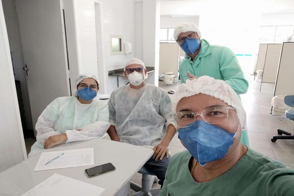 Professor Nilton, com equipamentos de proteção pessoal da área da saúde, com outros três integrantes do grupo Espia trajados da mesma forma.