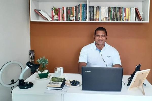 O professor Wesley Amaral está sorridente, numa mesa de escritório branca, em frente ao notebook, e atrás dele é possível ver uma estante com vários livros