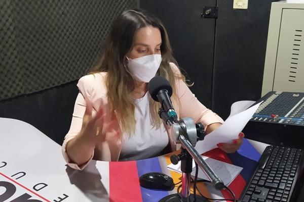 Aline Ferraz usando máscara, sentada diante do microfone enquanto lê um papel, no estúdio da Uesb Fm